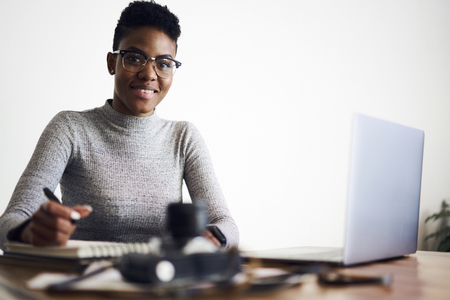Foto de Smiling portrait of skilled young afro american female developer controlling work of marketing experts analyzing role of advertising content in web retail - Imagen libre de derechos