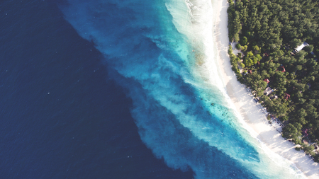 Photo for Top view aerial drone photo of stunning colored sea beach with crystalline water. incredibly beautiful blue ocean meet with powder-white seashore surrounded by tropical rainforest or palm trees jungle - Royalty Free Image