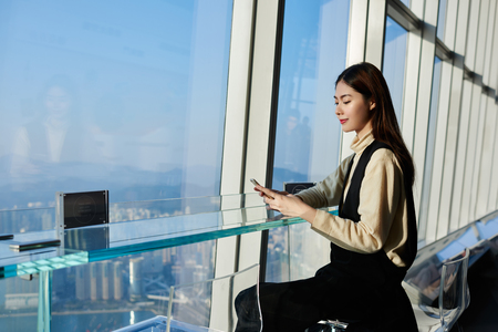 Photo for Woman successful lawyer is reading news in internet via cell telephone, while is waiting her client in modern interior with metropolitan city outside window. Young Japanese female is chatting on phone - Royalty Free Image
