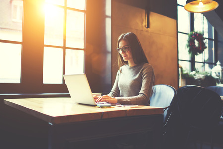 Foto de Experienced female freelancer typing message in online chat having internet conversation with manager requiring report about completed tasks and projects to - Imagen libre de derechos