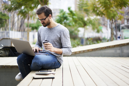 Photo pour Skilled male copywriter preparing proofreading copy to check spelling and grammar mistakes working outdoors - image libre de droit