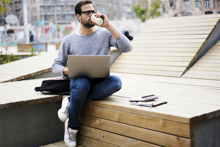 Photo pour Young male skilled freelancer  working without breaks drinking coffee outdoors trying to fulfill task of client in time - image libre de droit