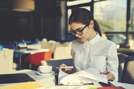 Photo for Skilled professional female administrative manager of coffee shop checking documentation for month before sending report to financier supervising working process and controlling stuff during revision - Royalty Free Image