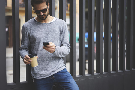 Photo pour Handsome bearded guy strolling on city street with coffee to go using online navigator to find right direction using modern smartphone - image libre de droit