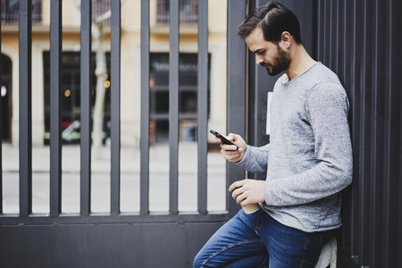 Photo pour Handsome bearded hipster guy spending time outdoors chatting in social networks with followers while waiting for friends meeting - image libre de droit