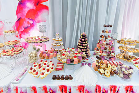 Photo for Wedding decoration with colorful cupcakes, eclairs, souffle, meringues, muffins, macarons and cookies. Elegant and luxurious event arrangement with sweets. Wedding dessert table in pink colors - Royalty Free Image