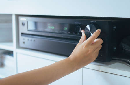 Photo for Hand turning on Home-theater amplifier system - Royalty Free Image