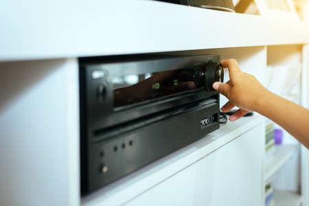 Foto de Hand turning on Home-theater amplifier system - Imagen libre de derechos