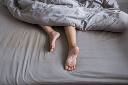 Foto de Close up of  barefoot,Feet and stretch lazily on the bed after waking up - Imagen libre de derechos