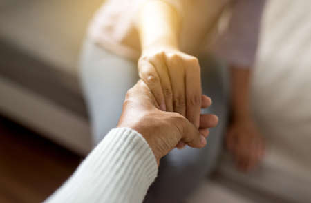 Foto de Man giving hand to depressed woman,Psychiatrist holding hands patient,Meantal health care concept,Selective focus - Imagen libre de derechos