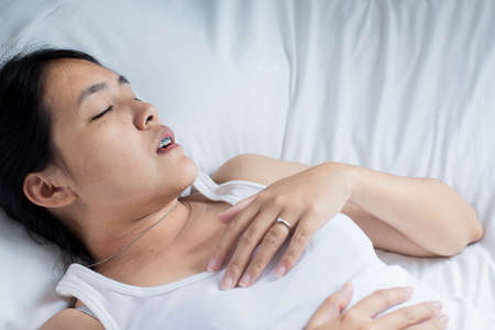 Photo pour Asian woman snoring because due to tired of work,Female snor while sleeping on bed - image libre de droit