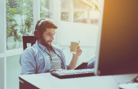 Foto de Portrait of handsome man with beard drinking hot coffee and listening to music online at modern home,Happy and smiling,Relax time - Imagen libre de derechos