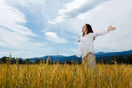 Foto de Girl holding arms up against blue sky - Imagen libre de derechos