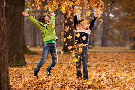 Boy and girl playing with fallen leaves in autumn