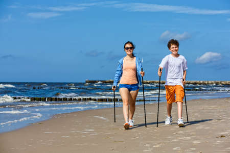 Photo for Nordic walking, young people working out on beach - Royalty Free Image