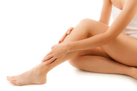 Photo pour Woman massaging legs sitting on a white background - image libre de droit