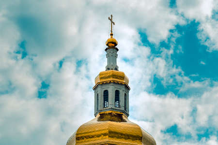 The dome of the Orthodox Church is covered with gold and is crowned with a cross against a blue sky with white clouds close-up