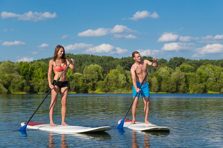 Photo pour Young attractive couple on stand up paddle board in the lake, SUP - image libre de droit