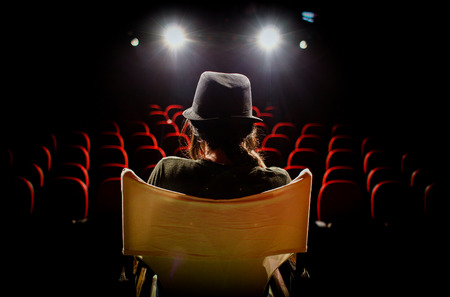 Photo pour Young woman on director's chair on stage, in front of empty seats and in between curtains - image libre de droit