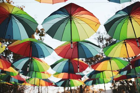 Photo pour Rainbow colored umbrellas hang in a public park - image libre de droit