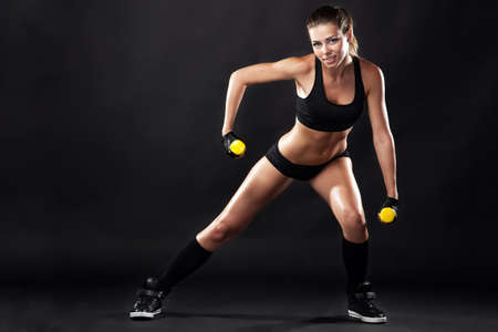 Beautiful slim woman with dumbbells, black background