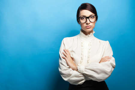 Strict woman in large glasses, blue background