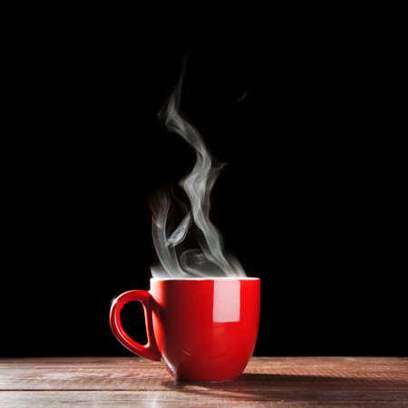 Photo pour Steaming coffee cup on dark  - image libre de droit