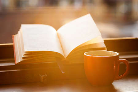 Photo pour Books and a coffee cup on a windowsill - image libre de droit
