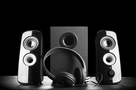 Photo for Modern black sound speakers and headphones on dark background - Royalty Free Image