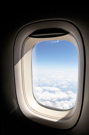 cloudscape of window at flying airplane