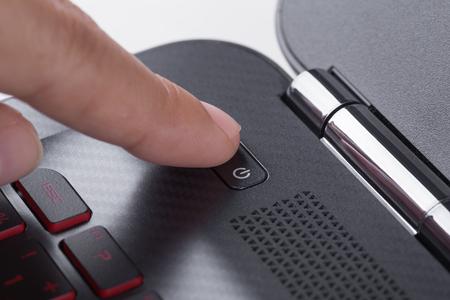 Photo pour finger pushing power button on a laptop keyboard - image libre de droit