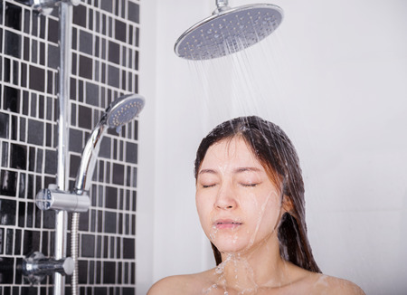 Photo for Woman is washing her hair and face by rain shower head - Royalty Free Image