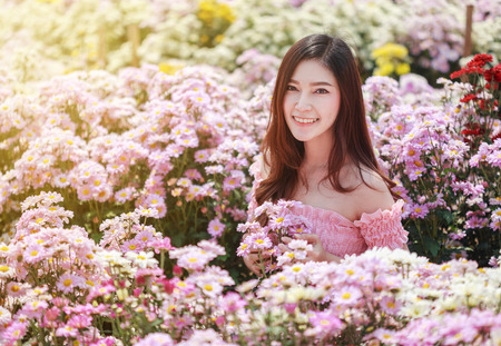 Foto de beautiful woman in colorful chrysanthemum glower garden  - Imagen libre de derechos