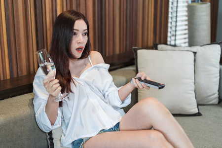 Shocked young woman sitting on a sofa and watching tv with remote control