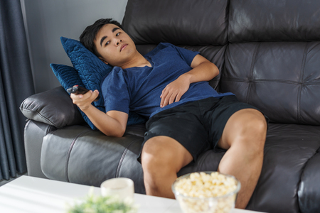 Photo pour young bored man watching tv and sitting on sofa in the living room - image libre de droit