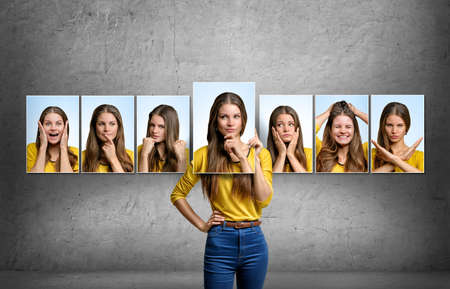 Photo pour Young beautiful girl holds and changes her face portraits with different emotions. - image libre de droit