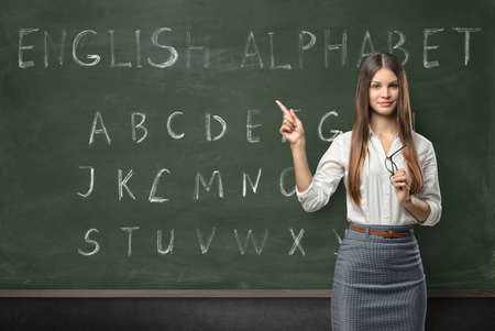 Foto de Attractive young woman teacher in a classroom teaching the English language with a hand written alphabet on the chalkboard - Imagen libre de derechos