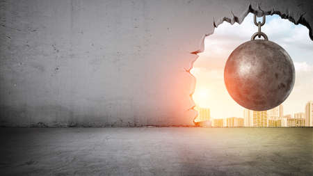 Foto de A black wrecking ball hanging inside the opening in a concrete wall showing city landscape. - Imagen libre de derechos