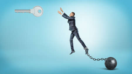 Photo pour A businessman chained to an iron ball tries to jump and reach a large silver key hanging above. - image libre de droit