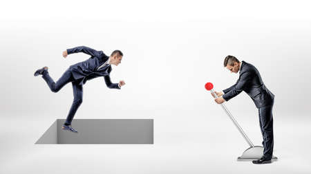 Foto de A businessman runs on white ground while a square hole controlled by a man on a lever opens right under his feet. - Imagen libre de derechos