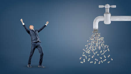 Photo for A small victorious businessman stands with raised arms near a giant water faucet leaking a lot of dollar bills. - Royalty Free Image