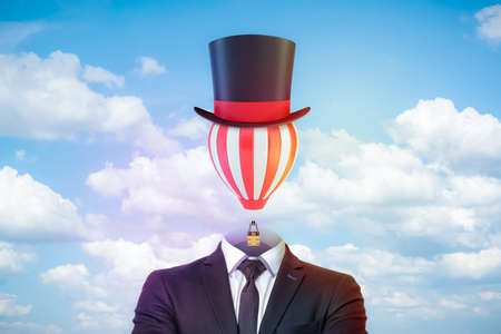 Photo pour Male figure in smart suit, tie and tophat with a striped hot-air balloon instead of the head against blue sky with white clouds. - image libre de droit