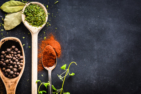wooden spoons with spices and herbs on textured black background