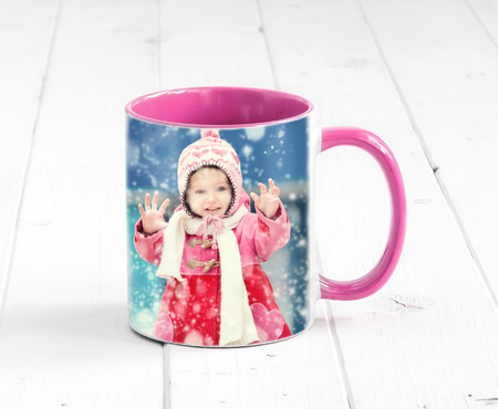 Foto de Pink cup with bright pink handle sitting on the table, with a print of girl - Imagen libre de derechos