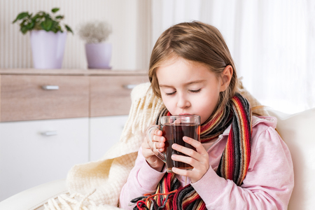 Photo for Little ill girl in scarf drinking tea - Royalty Free Image
