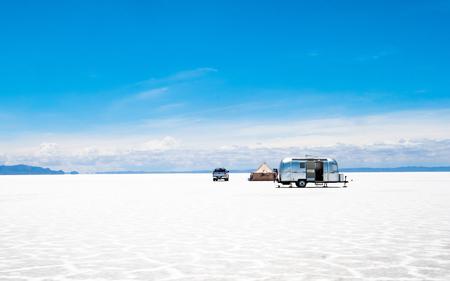 Photo pour Car with camping trailer and tent set up among sunshine Salar de Uyuni - image libre de droit