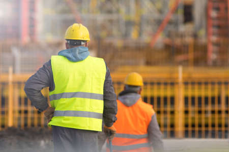 Photo pour Two builders in yellow and orange at the construction site - image libre de droit