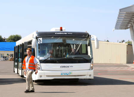 Foto de Kyiv, Ukraine - August 30, 2019: Bus and unidentified airport worker. Igor Sikorsky Kyiv International Airport Zhuliany is one of the two passenger airports of the Ukrainian capital Kyiv, the other being Boryspil International Airport. It is owned by the  - Imagen libre de derechos