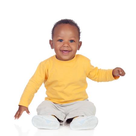 Foto de Adorable african baby sitting on the floor isolated on a white background - Imagen libre de derechos