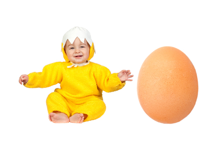 Nice baby chick disguised with a big egg at his side isolated on a white background